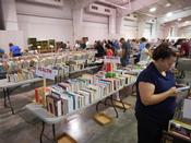 Customer browsing tables full of books at Friends of the Library Book Sale.