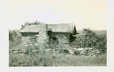 "From the Library collection, on back is written ""On road toward Branson.  House is gone now. Typical log house."" No date given."