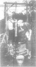 Ex-moonshiner Newt Bruffett and his wife, Alice at a well at one of their haunted homes.