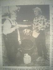 Newt Bruffett holding a condensing barrel from a still. On right is Stone County Sheriff Tommy Walker.